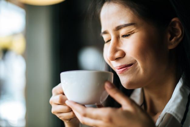 Portrait, femme asiatique, sourire, détendre, dans, café, café café Photo gratuit
