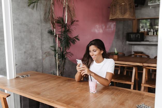 Portrait De Femme Assise Dans Un Café Et Bavarder Avec Sourire Sur Smartphone Photo gratuit