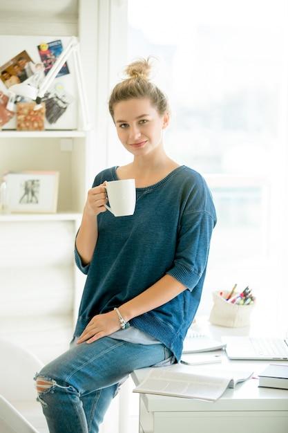 Portrait d'une femme attirante à demi assise à la table Photo gratuit