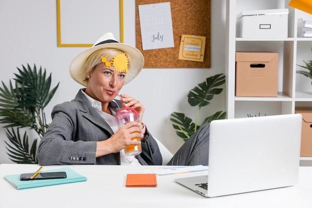 Portrait de femme au bureau préparée pour les vacances d'été Photo gratuit