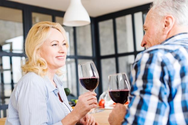 Portrait d'une femme blonde âgée buvant le vin avec son mari dans la cuisine Photo gratuit