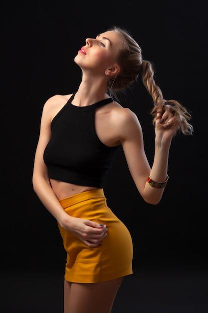Portrait de femme blonde jeune beauté posant en manteau de cuir et jupe fashion jaune sur fond isolé noir. Photo Premium