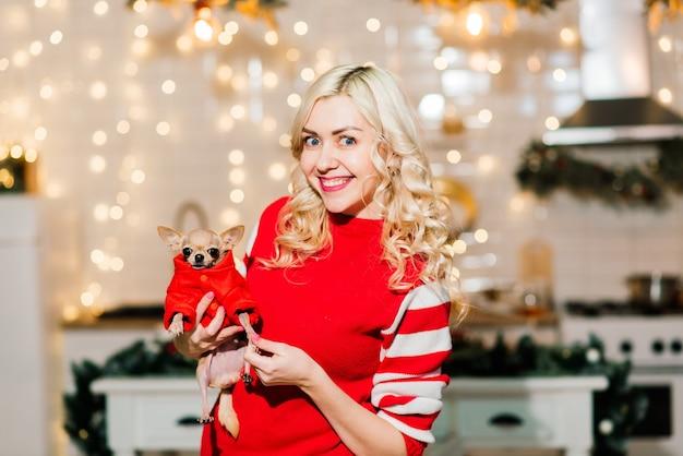 Portrait De Femme Blonde Portant Noël Santa Tenant Des Chiens Chihuahua En Costume De Noël Dans La Cuisine Avec Décoration De Noël, Souriant Et Regardant La Caméra. Photo Premium