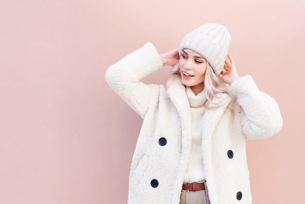Portrait d'une femme blonde souriante en vêtements d'hiver à la recherche de suite sur fond rose. Photo Premium