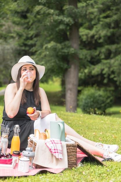 Portrait, femme, boire, jus, tenue, pomme, main, pique-nique Photo gratuit