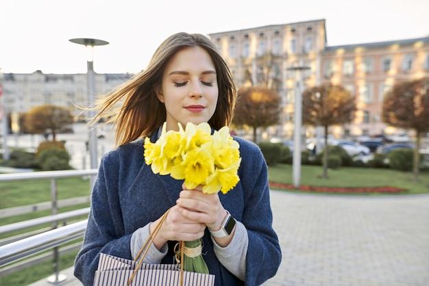 Portrait de femme avec bouquet de jonquilles de fleurs printanières jaune Photo Premium
