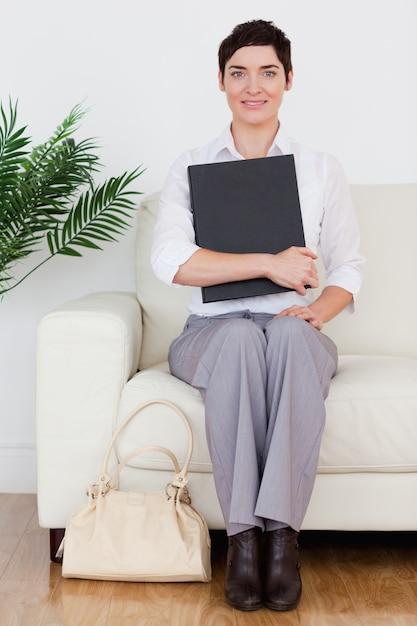 Portrait D'une Femme Brune Aux Cheveux Courts, Assis Sur Un Canapé Photo Premium