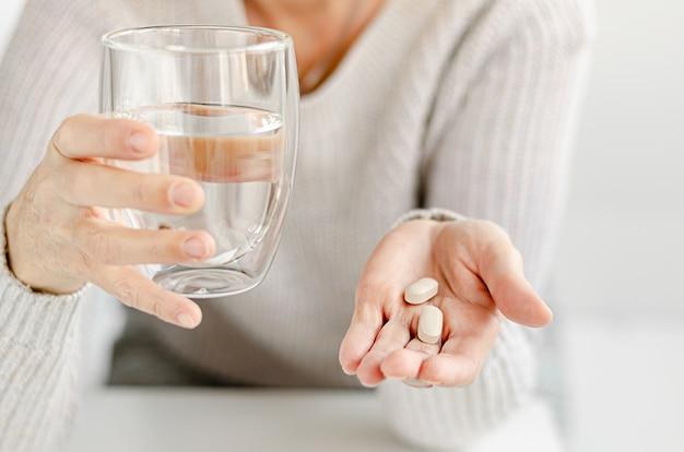 Portrait D'une Femme Caucasienne Sesior Tenant Une Pilule Et Un Verre D'eau. Espace Copie Photo Premium