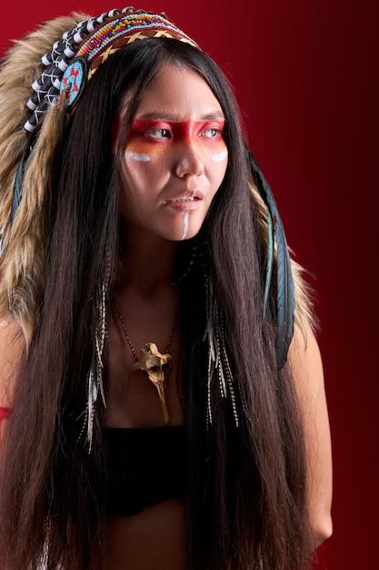 Portrait De Femme Chamanique Indienne Mystérieuse Avec Plume Indienne Portant Et Maquillage Coloré à L'écart, Isolé Sur Mur Rouge Photo Premium