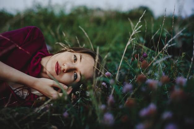 Portrait de femme charmante femme en chemise violette se trouve sur la gree Photo gratuit