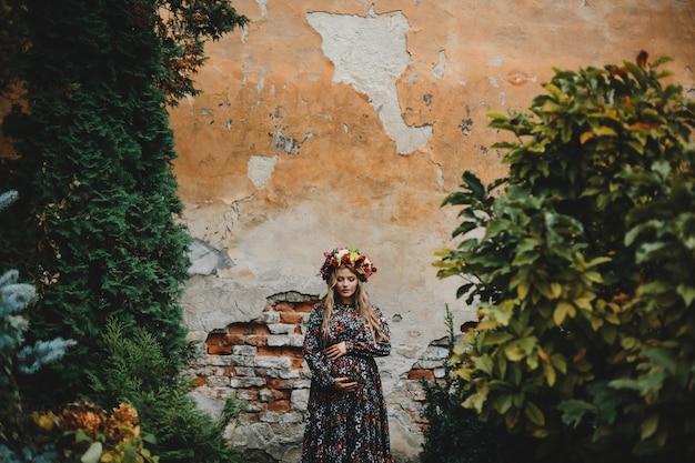 Portrait de femme charmante femme enceinte en robe à fleurs pose Photo gratuit