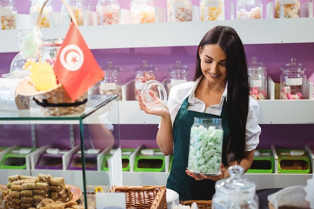 Portrait De Femme Commerçant Tenant Pot De Bonbons Turcs Au Comptoir Photo gratuit