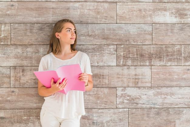 Portrait, de, femme, debout, devant, mur, tenue, livre rose, regarder loin Photo gratuit
