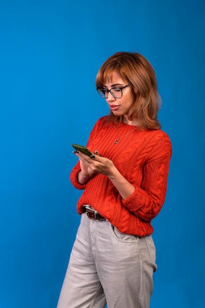 Portrait D'une Femme Décontractée Souriante Tenant Un Smartphone Sur Fond Bleu. Photo Premium