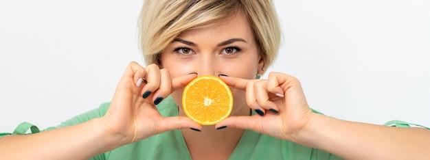 Portrait De Femme Diététiste Tenant Et Montrant Une Tranche D'orange Photo Premium
