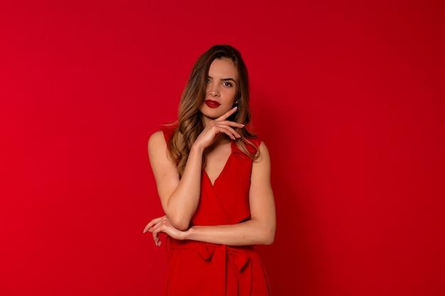 Portrait De Femme Enchanteresse Souriante En Robe Rouge Posant Photo gratuit