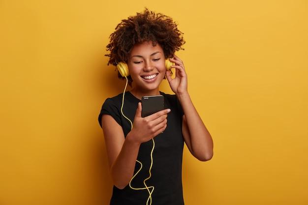 Portrait De Femme énergique Joyeuse Avec Une Coiffure Frisée, Regarde Une Vidéo Drôle, Porte Un Casque Connecté Au Smartphone Isolé Sur Fond Jaune Photo gratuit