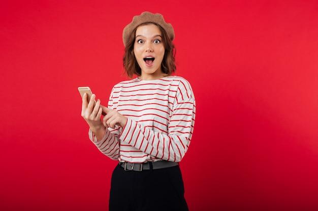 Portrait D'une Femme Excitée Portant Un Béret Tenant Un Téléphone Mobile Photo gratuit