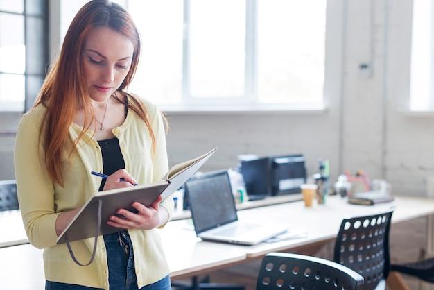 Portrait de femme faisant des notes dans le bloc-notes sur le lieu de travail Photo gratuit