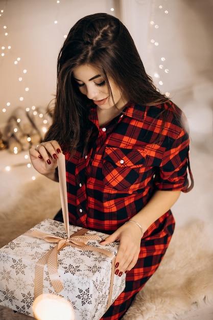 Portrait De Femme Femme Enceinte En Chemise à Carreaux Pose Dans Une Chambre Confortable Avec Arbre De Noël Et Ouvre Pr Photo gratuit