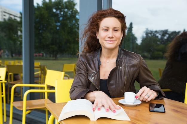 Portrait de femme heureuse avec expresso et bon livre au café Photo gratuit