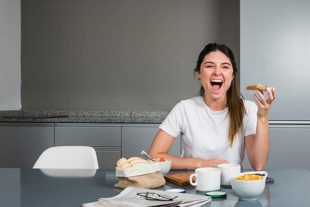 Portrait d'une femme heureuse prenant son petit déjeuner sain Photo gratuit