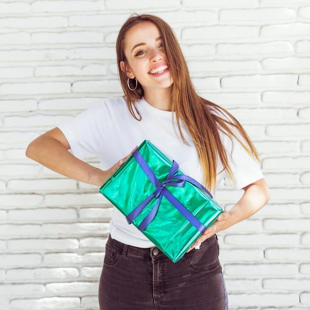 Portrait d'une femme heureuse tenant un coffret vert Photo gratuit