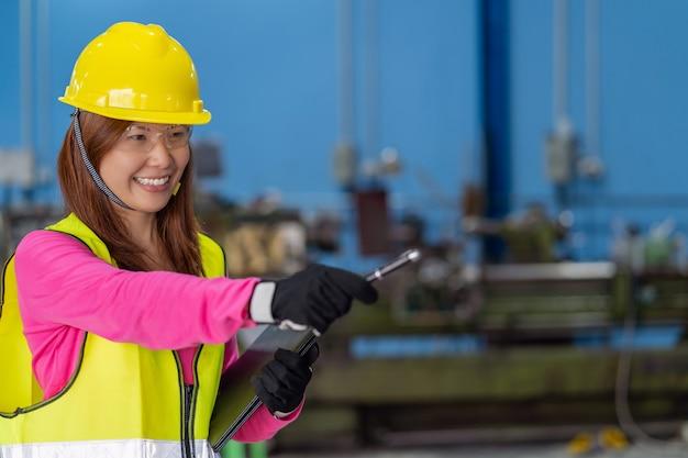 Portrait de femme ingénieur des ventes asiatique vérifiant la liste des travaux en papier sur le flou de la photo Photo Premium