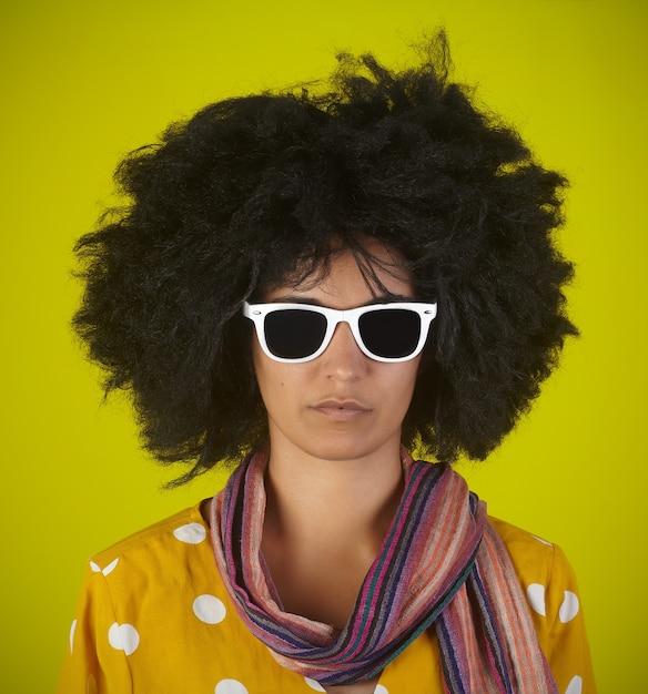 Portrait D'une Femme Intrigante Indienne Avec Une Coiffure Afro Bouclée Et Des Lunettes Blanches Sur Mur Jaune Photo Premium