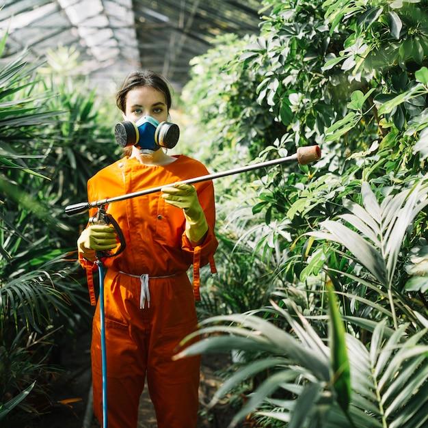 Portrait, femme, jardinier, porter, masque pollution, pulvérisation, insecticide, sur, usines Photo gratuit