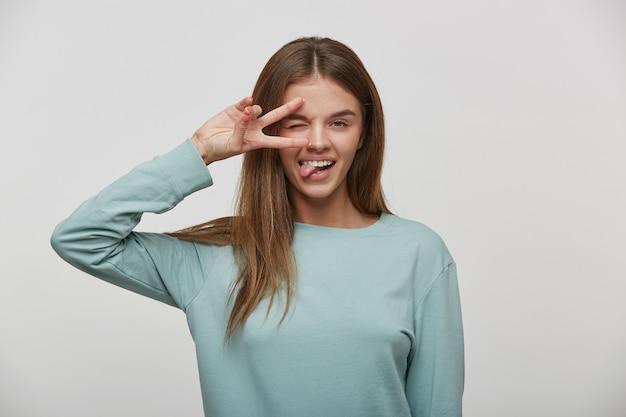 Portrait D'une Femme Jeune Cheveux Bruns Heureux, Affable, Sympathique, Joyeux Montrant Le Geste De Paix Et Collant Sa Langue Photo gratuit