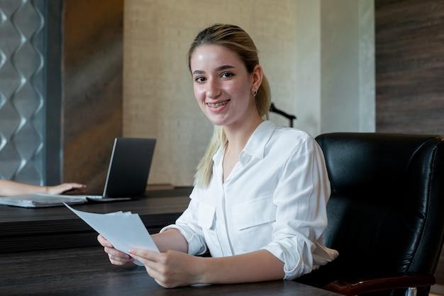 Portrait De Femme Jeune Employé De Bureau Assis Au Bureau Avec Des Documents à L'ennui Et Surmené Assis Au Bureau Photo gratuit