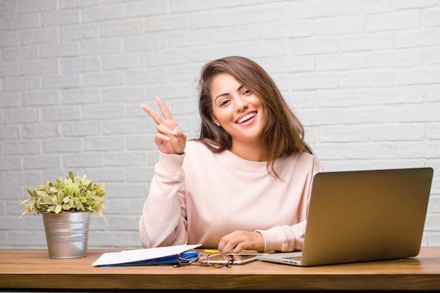 Portrait de femme jeune étudiante latine assise sur son bureau amusant et heureux, positif et naturel, faisant un geste de victoire, concept de paix Photo Premium