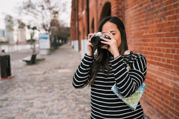 Portrait De Femme Jeune Photographe à L'aide D'un Appareil Photo Numérique Professionnel à L'extérieur. Concept De Photographie Photo gratuit
