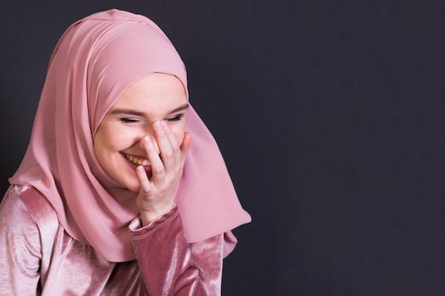 Portrait de femme joyeuse, debout dans un décor noir Photo gratuit