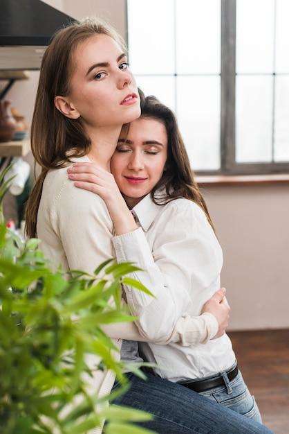 Portrait de femme lesbienne embrassant sa copine en regardant la caméra Photo gratuit
