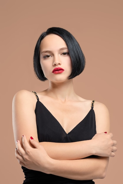 Portrait de femme mélancolique en robe à bretelles. studio tourné sur beige Photo Premium