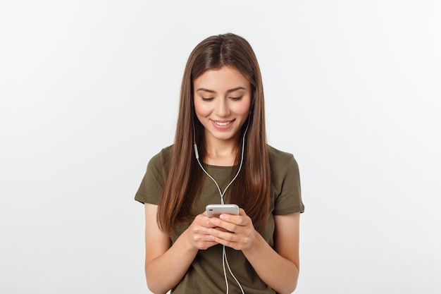 Portrait d'une femme mignonne joyeuse, écouter de la musique dans les écouteurs et danser isolé sur un blanc. Photo Premium