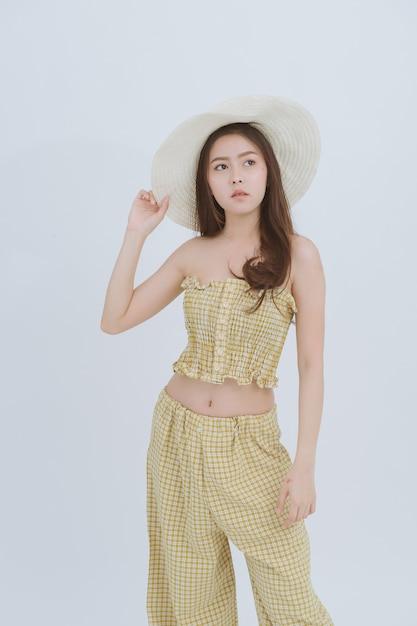 Portrait de femme mince asiatique coiffé d'un grand chapeau sur fond isolé blanc. Photo Premium