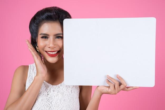 Portrait de femme de mode affichant une bannière blanche Photo gratuit