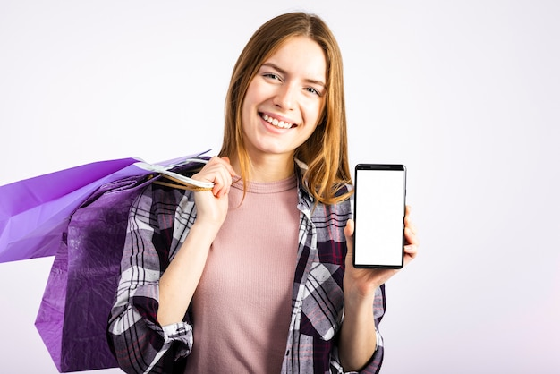 Portrait femme montrant un téléphone à la caméra Photo gratuit
