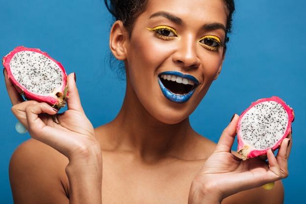 Portrait De Femme Mulâtre Heureux Avec Maquillage Lumineux Bénéficiant De Fruits Pitaya Mûrs Coupés En Deux Sur Le Mur Bleu Photo gratuit