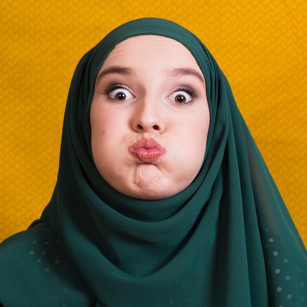 Portrait de femme musulmane faisant une drôle d'expression du visage en face de fond jaune Photo gratuit