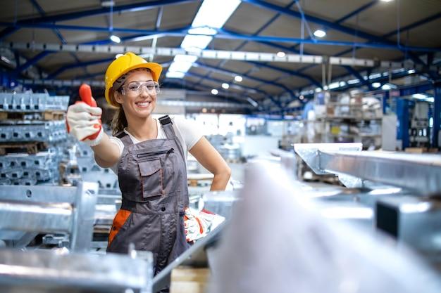 Portrait De Femme Ouvrière D'usine Tenant Les Pouces Vers Le Haut Photo gratuit