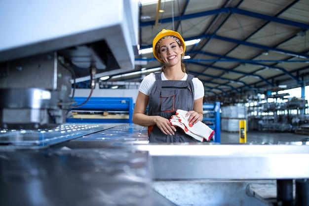 Portrait De Femme Ouvrière D'usine En Uniforme De Protection Et Casque Debout Par Machine Industrielle à La Ligne De Production Photo gratuit