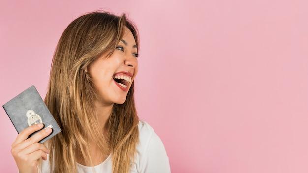 Portrait, femme, passeport, main, rire, contre, fond rose Photo gratuit