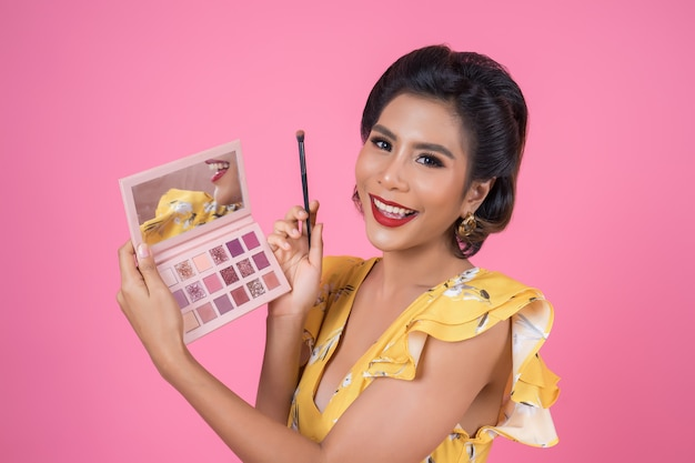 Portrait de femme avec pinceau de maquillage et cosmétique Photo gratuit