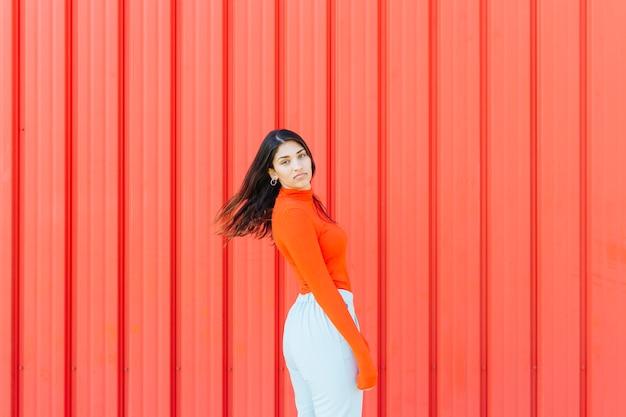 Portrait de femme posant sur fond métallique ondulé rouge Photo gratuit