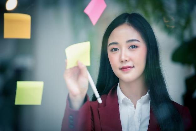 Portrait D'une Femme Qui écrit Sur Un Bloc De Papier Collant Sur La Paroi De Verre Photo Premium