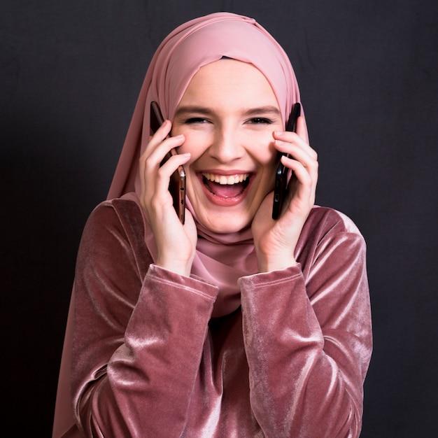 Portrait de femme qui rit en regardant la caméra tout en parlant au téléphone portable Photo gratuit